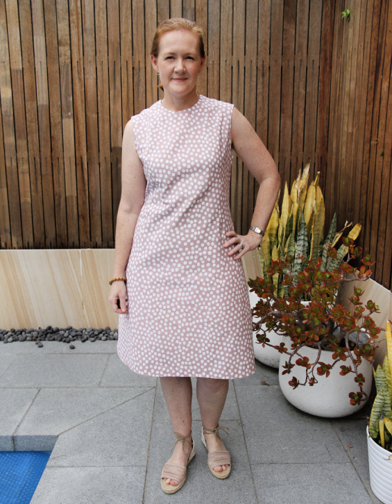 a white lady posing in a pink and white polka dot dress next to plants in white pots