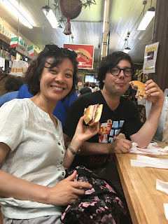 Greig Roselli and his friend eat a mufaletta at lunch bar at Central Grocery on Rampart Street in the French Quarter neighborhood of New Orleans, Louisiana