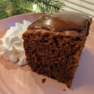 Slice of gingerbread cake with shiny date syrup sauce on top, in front of a lit christmas tree.