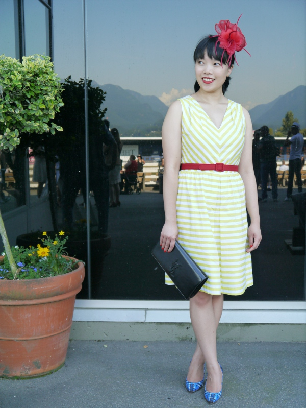 Vancouver blogger Lisa Wong of Solo Lisa wears a yellow-and-white striped day dress from JACOB, a red fascinator from Fine Finds, and a red belt along with a Saint Laurent 'Belle de Jour' black patent clutch and patterned cobalt-and-blue J. Crew 'Everly' pumps.