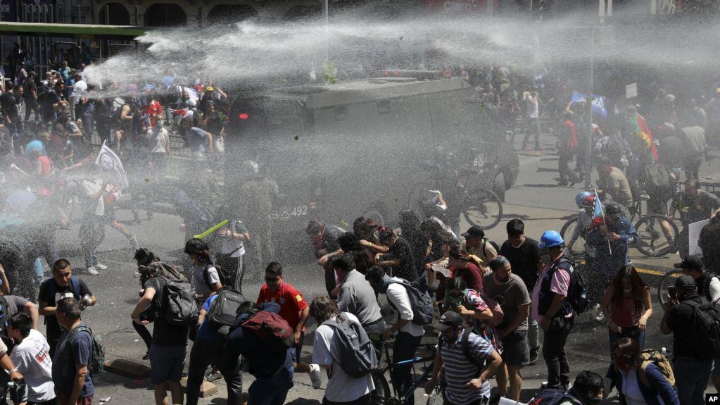 Manifestantes son rociados con un cañón de agua por la policía durante una protesta en Santiago, Chile / AP