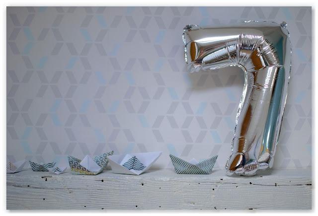 ballon argenté en forme de 7, bateaux origami en papier et fond tapisserie chevron