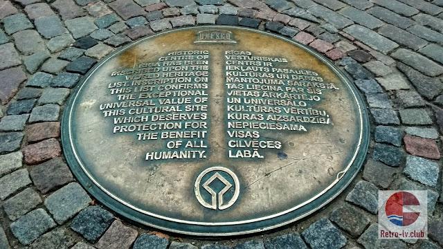 Табличка на Домской площади, которая сообщает, что исторический центр Риги включён в список Всемирного наследия ЮНЕСКО