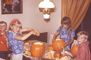 Four young children carving pumpkins