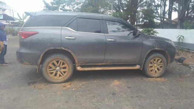 Mobil yang saya naiki kena lumpur karena kesasar di lahan belantara mengikuti arahan Google Maps, bannya penuh dengan lumpur yang mengkerak.