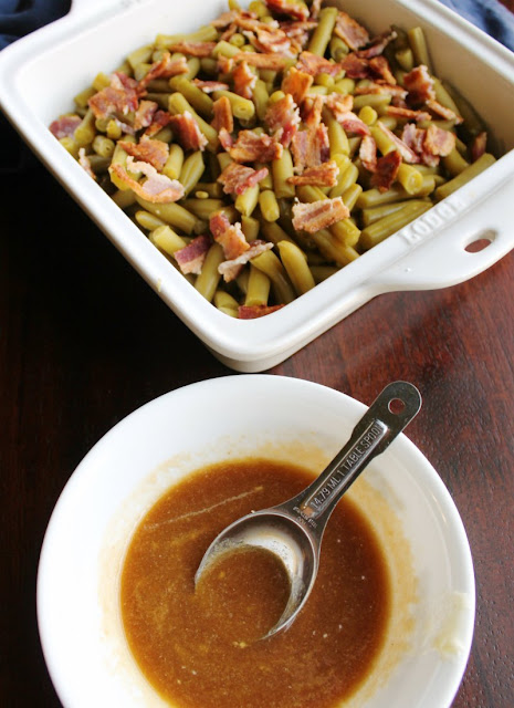 pan of green beans with bacon on top in background with bowl of sauce mixture for smothered green beans, ready to smother and cook