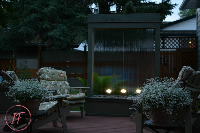 An amazing DIY Outdoor Water Feature for under $300 for a backyard deck or patio using recycled tempered glass. The outdoor fountain is also illuminated at night with solar flood lights. A budget-friendly water feature plus privacy screen for those who know how to rock power tools.