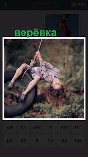 девочка катается на шине которая закреплена веревкой