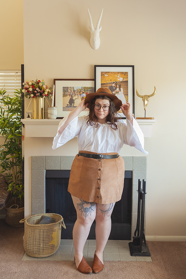 An outfit consisting of a brown panama hat, a white ruffled off the shoulder top with 3/4 bell sleeves, tucked into a brown button down mini skirt and brown d'orsay flats.