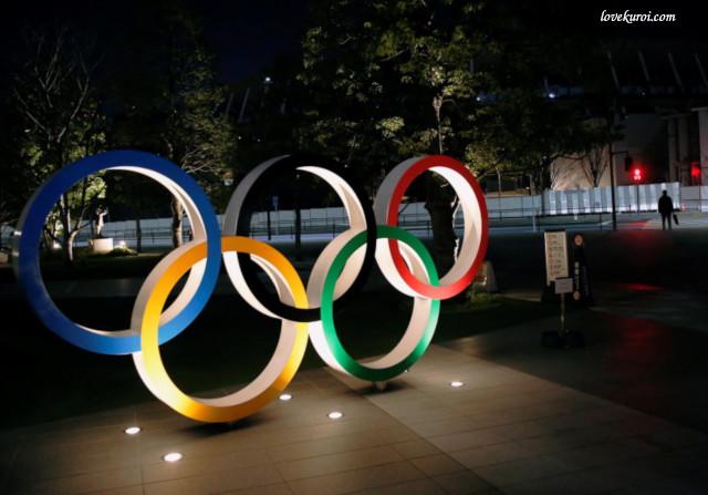 Олимпийские кольца освещаются перед Национальным стадионом в Токио