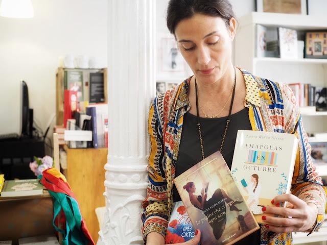 Retrato de Laura Riñón sujetando las distintas ediciones de su novela Amapolas en octubre