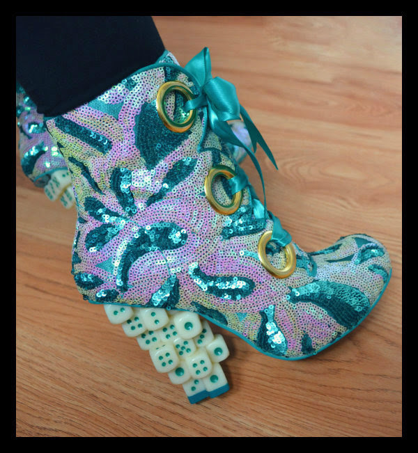 close up of sequins dice heeled boots on foot
