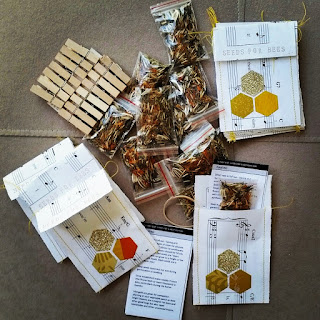 Materials for distributing Seeds for Bees are scattered: paper collaged packets which will contain instructions and little snap-lock plastic bags of seeds.  A batch of wooden mini-pegs are ready to be used for attaching the seed packets to fences etc.