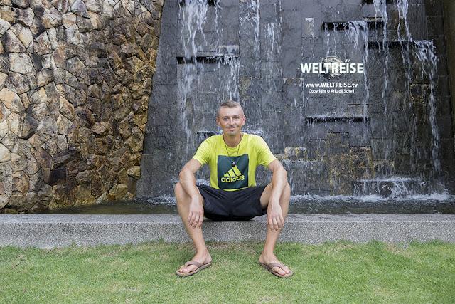 Arkadij vor Wasserfall im Urban Orchard Park in Kuala Lumpur. www.WELTREISE.tv