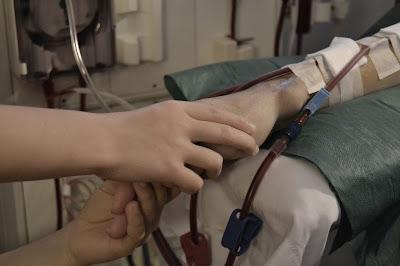 brazo de enfermo renal en sesión de hemodialisis con cateteres venoso y aretrial pinchados, manos de niños agarrando la mano del enfermo