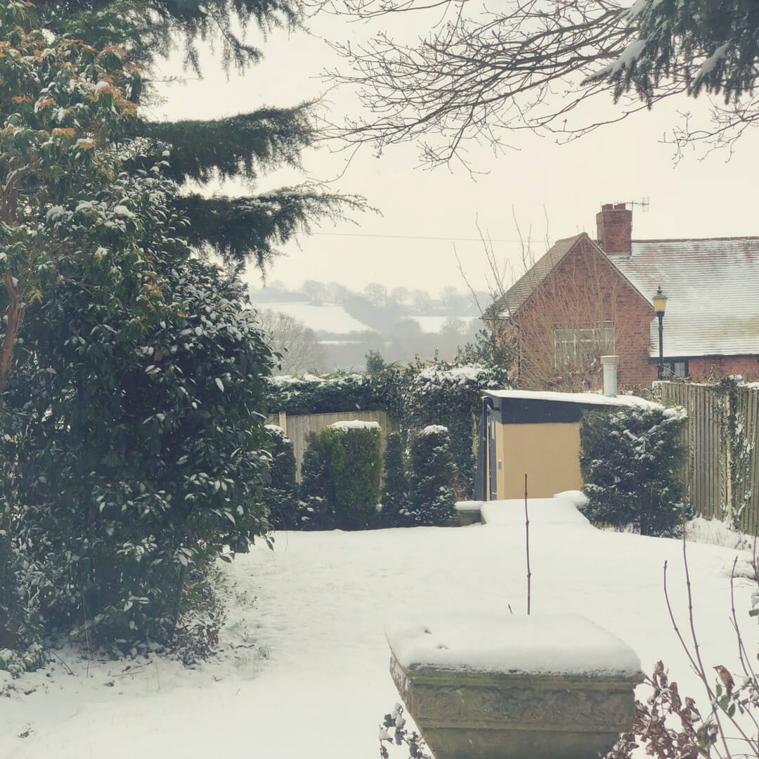"A snowy garden. A tree with snow covered leaves is on the left of the photograph, where there should be grass in the middle of the photo there's a white sheet. A house stands to the right in the background and behind the house there are snow-covered hills in the distance. White flecks cover the scene, snow is falling. Image for ""Post Comment Love 2nd - 4th March"""
