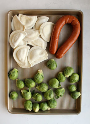 pierogi, whole brussels sprouts and whole sausage on sheet pan