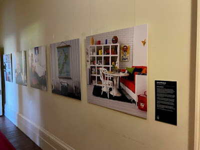 5 large blown up photos of 1/12 scale modern miniature scenes on display on a wall.