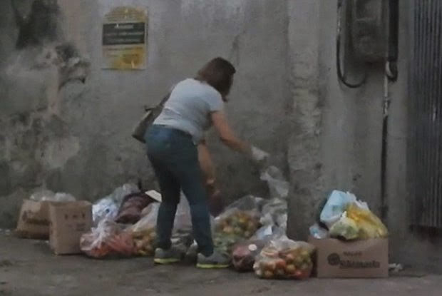 Mulher recolhe alimentos no lixo para servir em seu restaurante