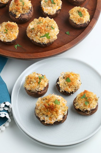 Cheesy Garlic Stuffed Mushrooms on white plate and wood platter