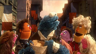 """Sesame Street Cookie's Crumby Pictures Les Mousserables. Cookie Monster, as """"Jean Bon-Bon,"""" learns how to identify the feelings of his fellow French friends by the way they look and act."""