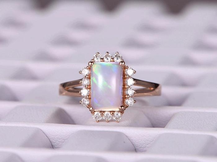 https://www.bbbgem.com/7x9mm-emerald-cut-african-opal-engagement-ring-14k-rose-gold-band-halo-stackable-ring-bridal-wedding-ring-split-shank-band-prong-setting/