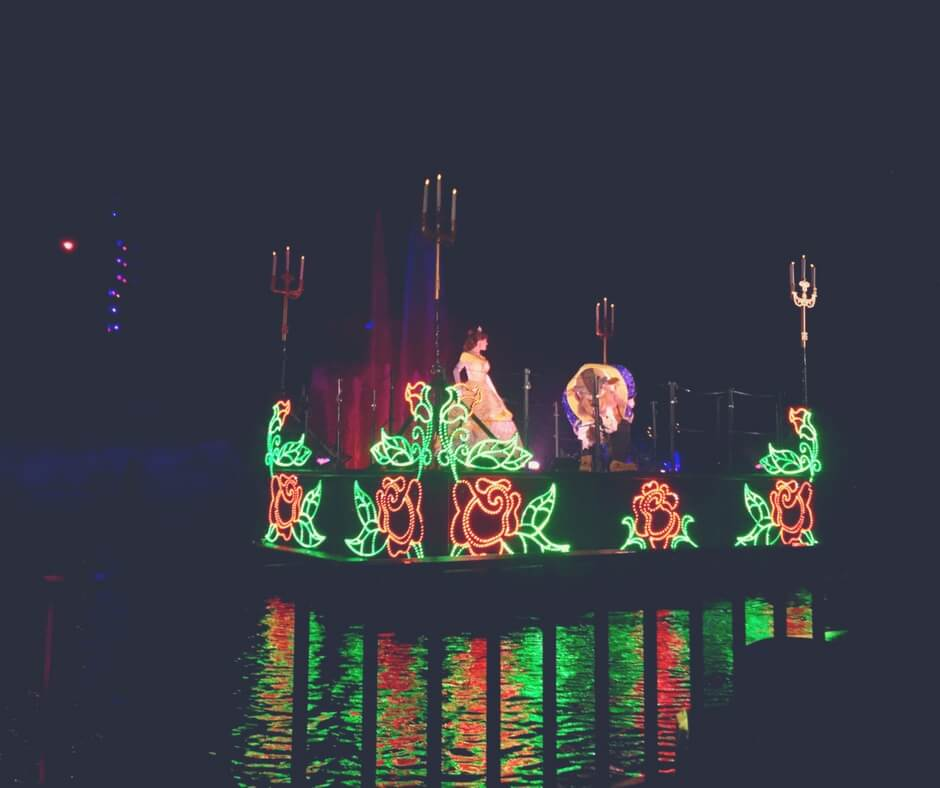 "A floating platform sits atop a darkened lake at night. On the sides of the platform are lights arranged in the form of roses, the lights are red for the rose and green for the leaves. Standing on top of the platform is Beauty and the Beast from the Disney movie. They are dancing. Image for ""How to get a much-needed rest at Disney's Hollywood Studios""."