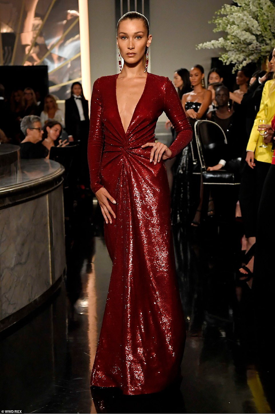 Bella Hadid flashes cleavage in plunging burgundy gown for Ralph Lauren's runway show during NYFW