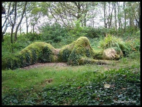Paisagem com um corpo humano, esculpido no solo, coberto de grama verde. #PraCegoVer