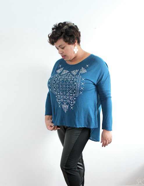woman wearing teal shirt with pearl designs