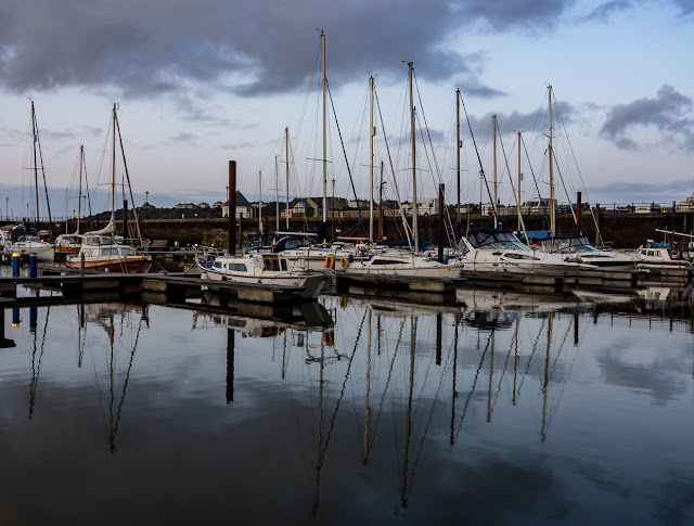 Photo of reflections on the still water at Maryport Marina