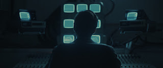 silhouette of person sitting in front of a bank of tv screens showing white noise