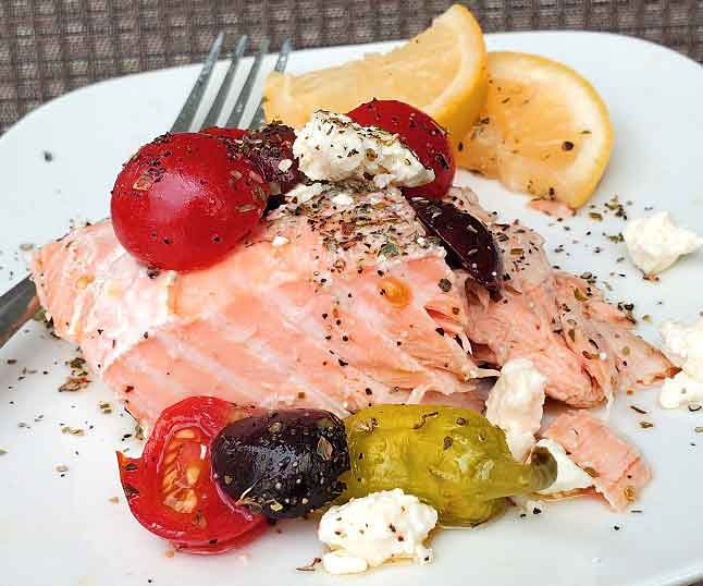 salmon baked and topped with a Greek salad dressing and vegetables