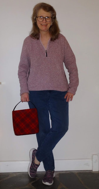 pink top with jeans and red plaid purse