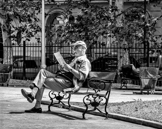 Un hombre sentado en banco de plaza al sol leyendo el diario.