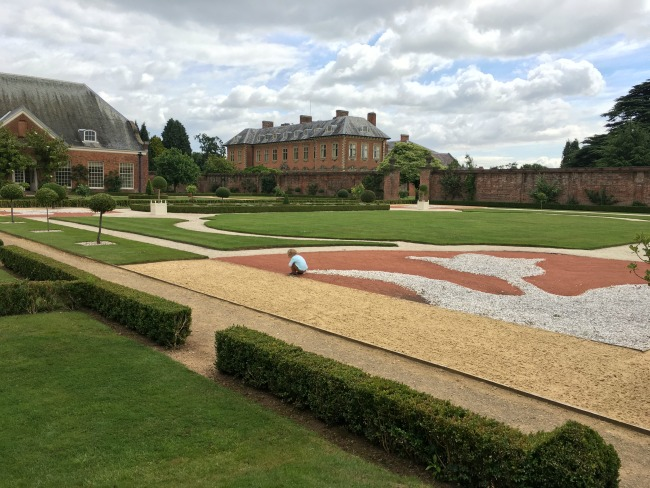 Tredegar-House-&-gardens-view-of-buildings-and-formal-gardens-with-toddler-crouched-down-playing