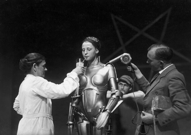 60 Iconic Behind-The-Scenes Pictures Of Actors That Underline The Difference Between Movies And Reality - The actress inside the Maria robot getting a reboot on the set of Fritz Lang's Metropolis.