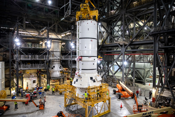 The aft segment of one of the Space Launch System's twin solid rocket boosters is about to be placed atop the mobile launcher inside Kennedy Space Center's Vehicle Assembly Building in Florida.