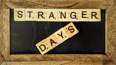 "A chalkboard with Scrabble tiles that spells out ""Stranger Days"""