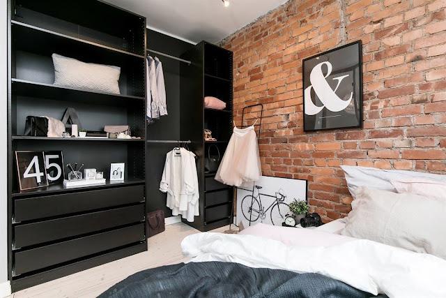 dulap negru si caramida expusa in dormitor