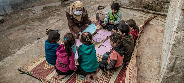 Un trabajador de la salud habla con los niños desplazados en el campamento sirio de Atma sobre sus esperanzas y preocupaciones.UNOCHA/Mahmoud Al-Basha