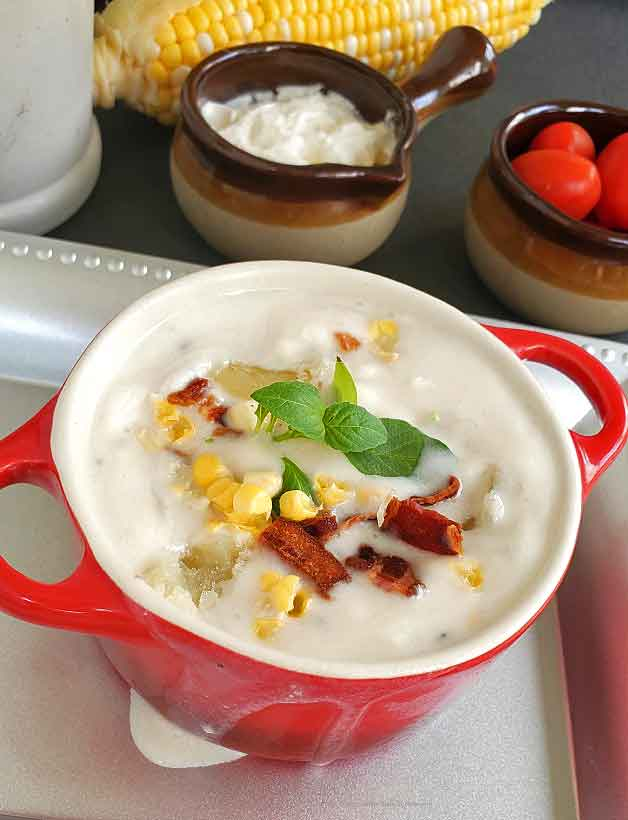 potato, bacon and corn soup in a red crock bowl