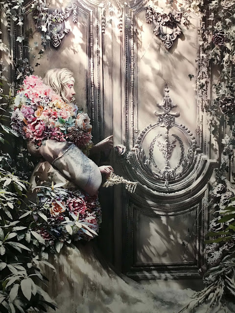 Fairy-tale blonde woman dressed in a flowery dress holding a key to a large ornamented wooden door.
