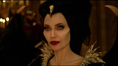 """Maleficent 2"" movie still where Angelina Jolie covers her horns with a scarf before meeting the king and queen of Ulstead"