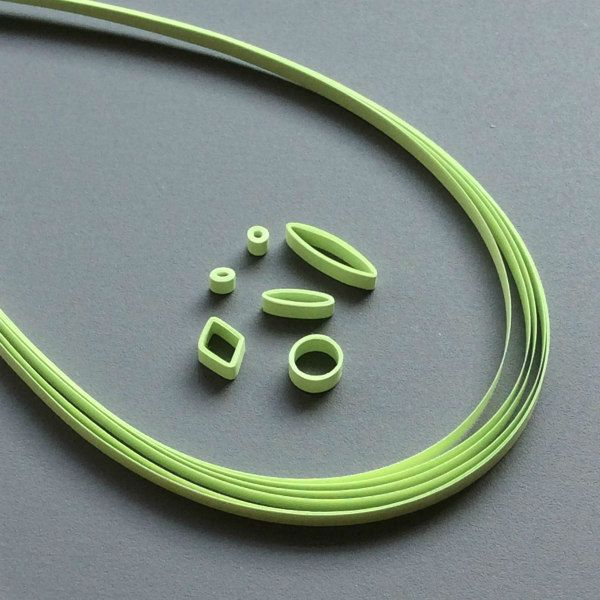 green quilling strips and six quilled shape examples