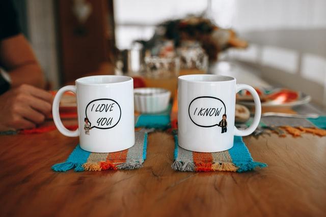 Dos tazas de café de color blanco sobre una mesa de madera