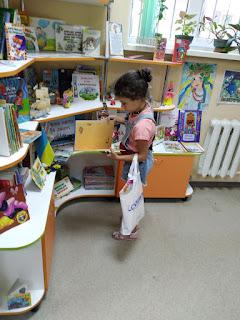 Девочка выбирает книги младший отдел бібліотека-філія №4 М.Дніпро