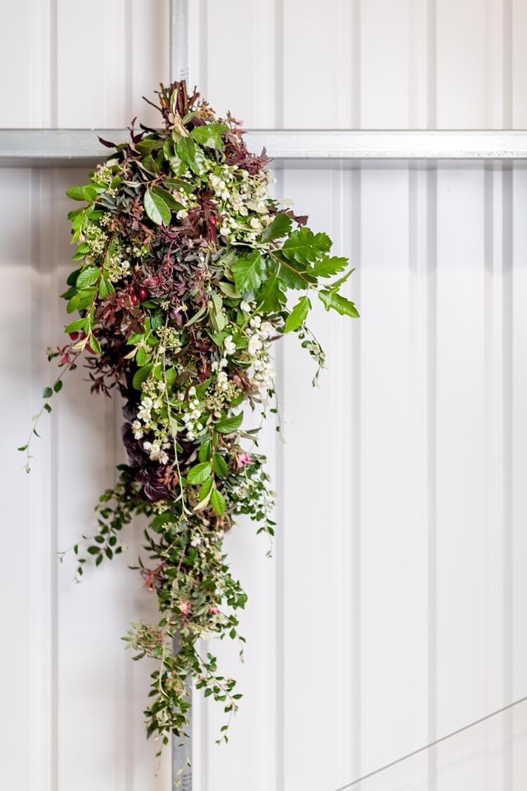 ramo de ducha con ramas de cotonaster, haya, roble, flores philadelphus y rosas trepadoras
