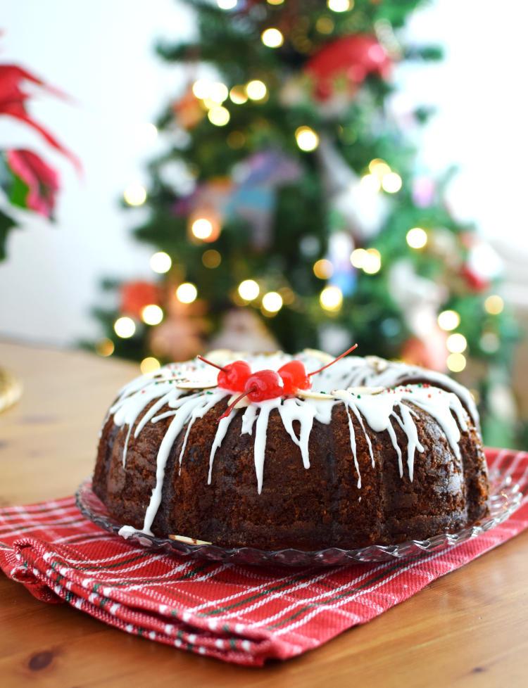 Torta negra con foto de decoraciones navideñas, arbolito y poinsettia