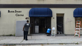 Workers clean the front of the building at 40 Baker Street on Wednesday afternoon. The Church of Scientology is moving into the building, renting out the office space and turning it into a headquarters for Scientology activities in Canada.
